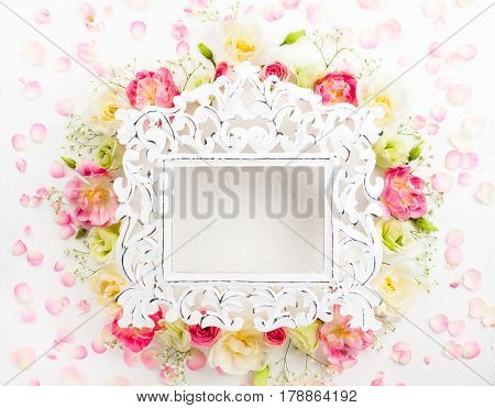 Festive flower concept : beautiful floral border with vintage frame on the white  background with copy space.  Flat lay.