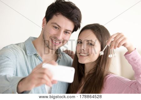 Young couple taking self portrait with smartphone showing keys, excited by apartment purchase. Beautiful woman and handsome man smiling at mobile phone camera to make selfie, holding keys of new flat
