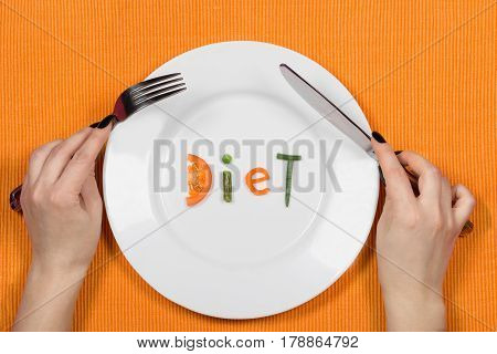 White plate with word diet made of pieces of vegetables on orange background. Female hands with fork and knife. Flat lay. Top view. Concept of dieting and healthy nutrition.
