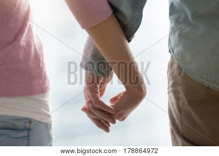 Young happy couple holding hands, touching fingers. Husband and wife supporting each other, teenagers dating, family sharing future, together concept. Close up, cropped image