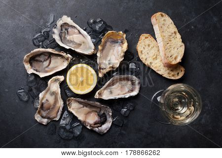 Opened oysters, ice and lemon with white wine over stone table. Half dozen. Top view