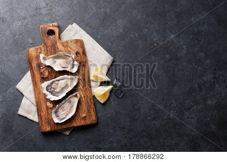 Opened oysters and lemon over board on stone table. Top view with copy space