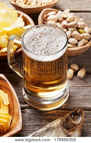 Lager beer mug and snacks on wooden table. Nuts, chips, fish