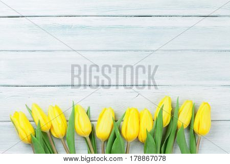 Easter card wooden background with yellow tulips. With space for your greetings