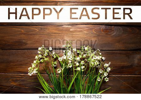 Beautiful spring flowers lily of the valley on woodward wooden background with white rectangle and the text of Happy Easter.