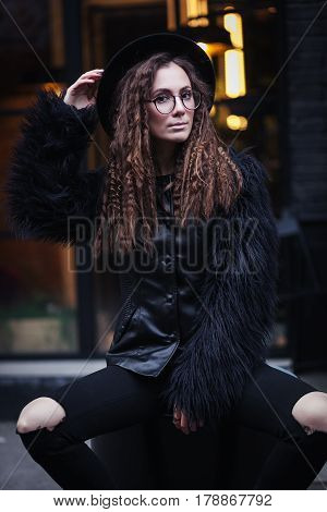 Portrait of a beautiful girl with brown eyes in glasses in a black hat and coat with fur sits on a barrel in the cityscape and looking in camera. The girl is like Harry Potter.
