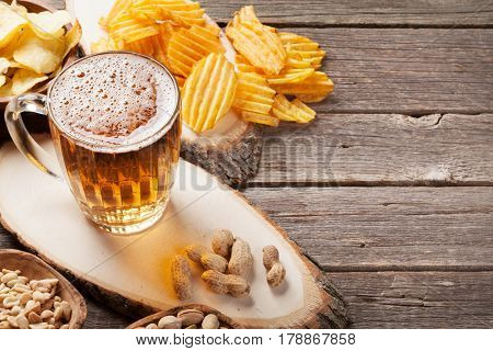 Lager beer mug and snacks on wooden table. Nuts, chips. With copyspace