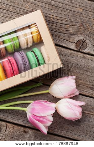 Colorful macaroon cookies and pink tulips bouquet on wooden table. Top view