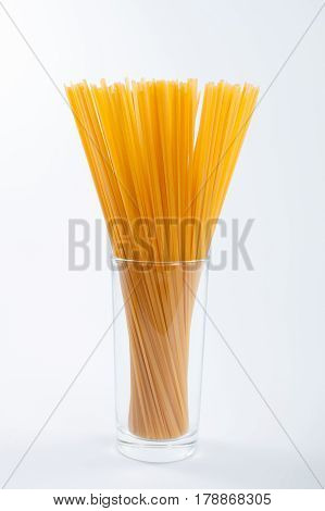 Handful of bavette pasta in highball glass on white background