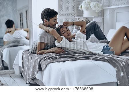Feeling safe and protected near him. Beautiful young couple resting and smiling while lying on the bed at home