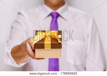 Male hand holding a gift box. Present wrapped with ribbon and bow. Christmas or birthday package. Man in white shirt and necktie.