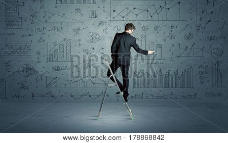 A businessman in modern stylish elegant suit standing on a small ladder and drawing pie and block charts on grey wall background with exponential progressing curves, lines, circles, blocks, numbers