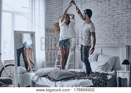 Just for fun. Full length of playful young couple holding hands and smiling while dancing on the bed at home