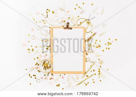 Beauty blog background. Clipboard and gold style feminine accessories pattern. Golden tinsel scissors pen rings necklace bracelet on white background. Flat lay top view.