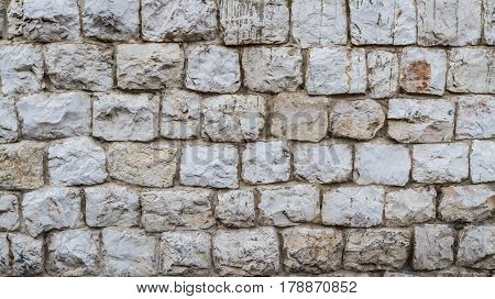 Stone wall background texture, white stone, background of old stone wall in Nazareth, Israel