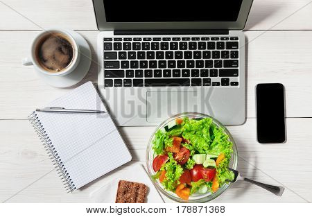 Healthy business lunch in office, top view of vegetable salad on white wooden desk near laptop computer keyboard. Salad bowl, coffee, mobile phone and notepad with pen flat lay. Snack at break time