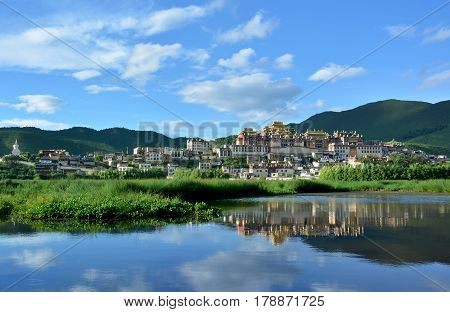 Songzanlin Tibetan Buddhist Monastery reflecting in the water of the sacred lake in Shangri-La Yunnan province China
