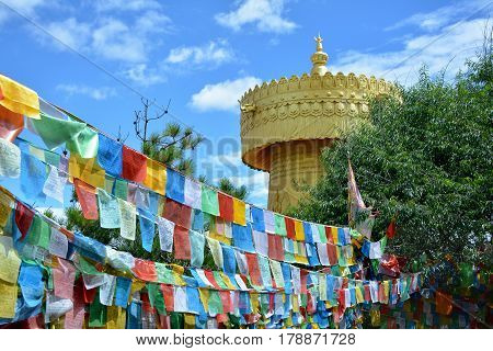 Colorful tibetian flags and biggest buddhist wheel in the world on the background of blue sky in Shangri-La China
