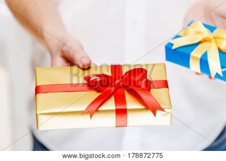 Male hands holding a gift boxes. Presents wrapped with ribbon and bow. Christmas or birthday blue, golden packages. Man in white shirt.