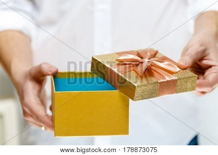 Male hands holding a gift box. Opened present wrapped with ribbon and bow. Christmas or birthday golden paper package. Man in white shirt.
