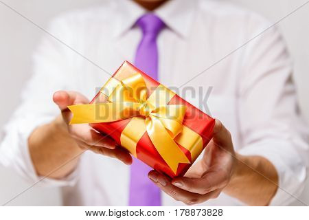Male hands holding a gift box. Present wrapped with ribbon and bow. Christmas or birthday red package. Man in white shirt and necktie.