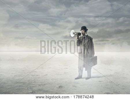 Businessman using a megaphone in the desert