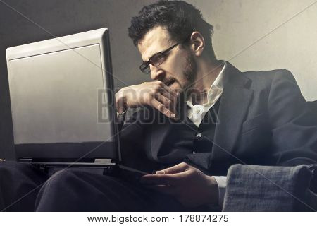 Pensive man looking at the screen of his laptop