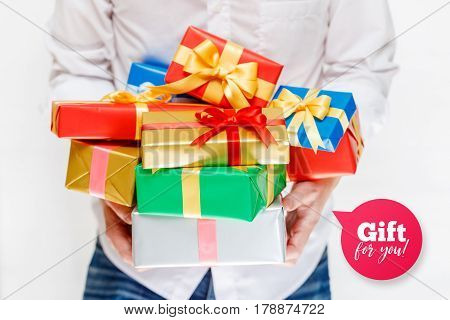 Male hands holding a gift boxes. Presents wrapped with ribbon and bow. Gift for you speech bubble. Man in white shirt.
