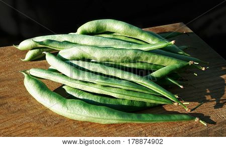 Green common beans (Phaseolus vulgaris) pods on wooden.