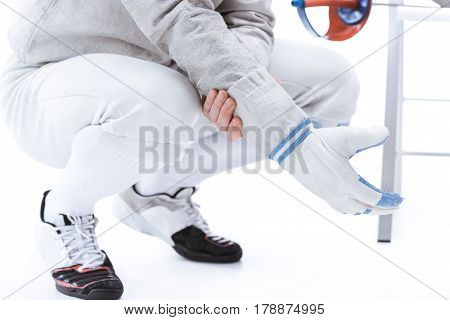 Cropped Shot Of Young Man Professional Fencer Wearing Glove On White