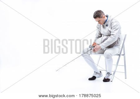 Young Man Professional Fencer Sitting On Chair With Helmet And Sword