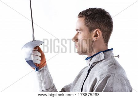 Side View Of Young Man Professional Fencer Holding Rapier On White