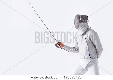 Side View Of Fencer In Uniform Training With Rapier On White