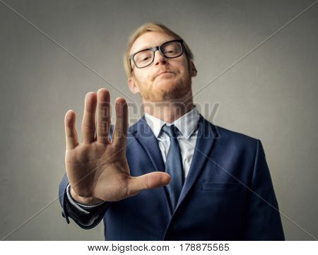 Young businessman stopping someone with a gesture of his hand