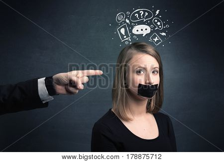 Caucasian business hand pointing at stressed female employee with drawn question, explamation marks above her head