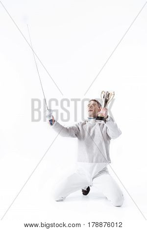 Portrait Of Smiling Fencer In Uniform With Champion's Goblet On White