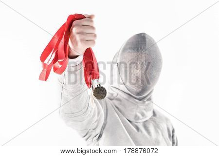 Portrait Of Professional Fencer In Fencing Mask Holding Medal On White