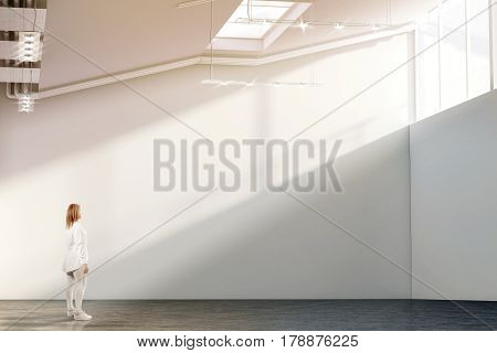 Woman walking near blank white wall mockup in modern gallery with sunset. Girl admires a clear big stand mock up in museum with contemporary art exhibitions. Large hall interior sunrise from windows