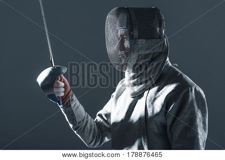 Portrait Of Professional Fencer In Fencing Mask With Rapier On Grey