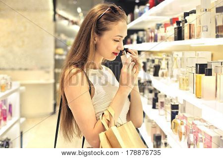 Beautiful girl choosing a perfume