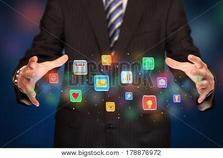 Elegant businessman holding colorful mixed media icons