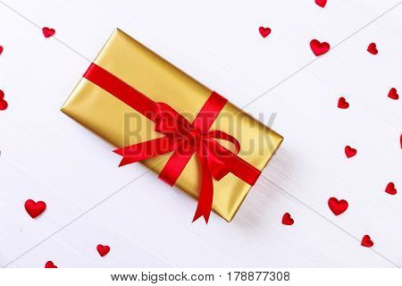 Gift box with red satin hearts. Present wrapped with ribbon and bow. Christmas or birthday golden paper package. On white wooden table.