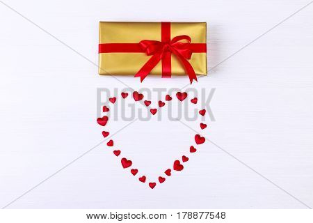 Gift box with red satin heart. Present wrapped with ribbon and bow. Christmas or birthday golden paper package. On white wooden table.