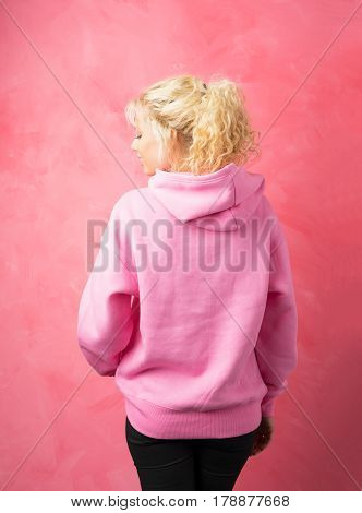 Woman in pink hoodie standing with her back turned