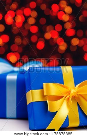 Gift boxes on blurred background. Colored presents wrapped with paper, bow and ribbons. Christmas or birthday packages. Celebration design.