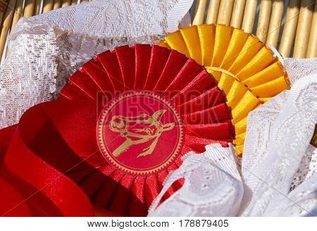 Award rosettes for winner in equestrian sport in red and yellow colors. Prize ribbons for horse show champion competition dressage.
