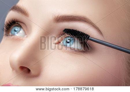 Mascara brush close up.  Make-up for blue eyes. Mascara applying, long lashes.