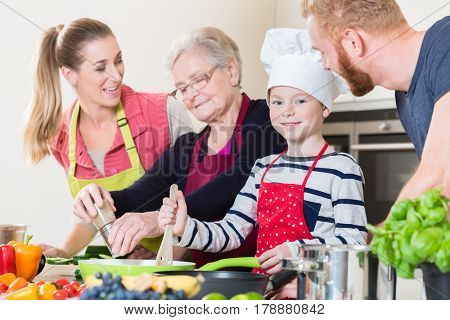 Family cooking in multigenerational household with son, mother, father and grandfather