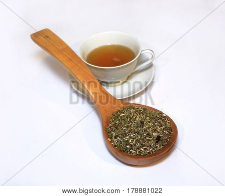 cup of tea and herbs on a wooden Net Worth on a white background
