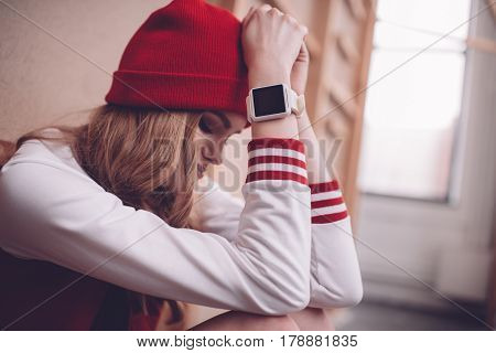 Upset Stylish Hipster Woman With Smartwatch Sitting And Looking Down